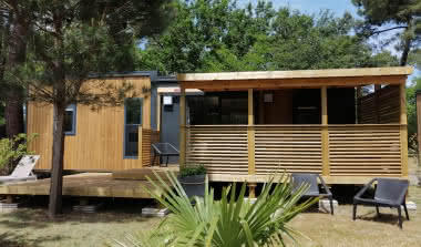 mobil-home-PRESTIGE-grand-confort-6-personnes-camping-les-ourmes-vue-exterieure-avec-4-fauteuils-de-jardin-et-2-bains-de-soleil